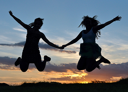 sillouettes of two women jumping